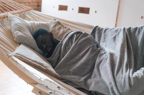 A photo of a man sleeping in a hammock