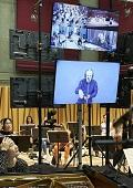Photo of the socially distanced orchestra and screens showing a feed of the conductor